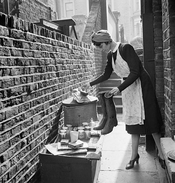 A British housewife puts out items for salvage during 1942. Ministry of Information Second World War Official Collection